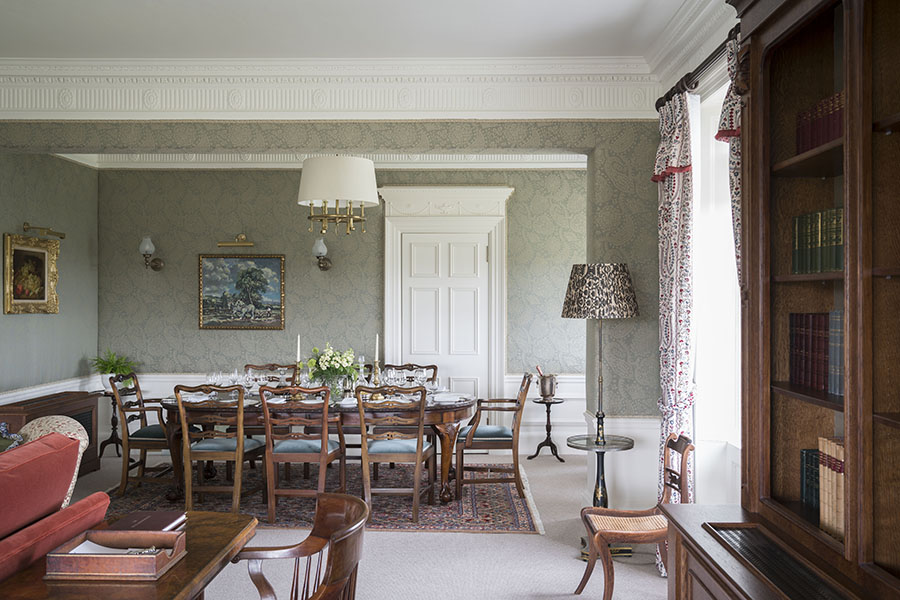 A dining room with table and eight chairs in the royal Lochnagar Suite