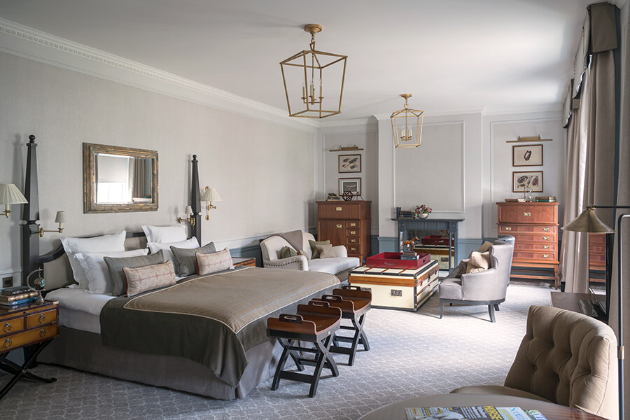 A large Manor bedroom with king-sized bed and seating for four around a chest ottoman