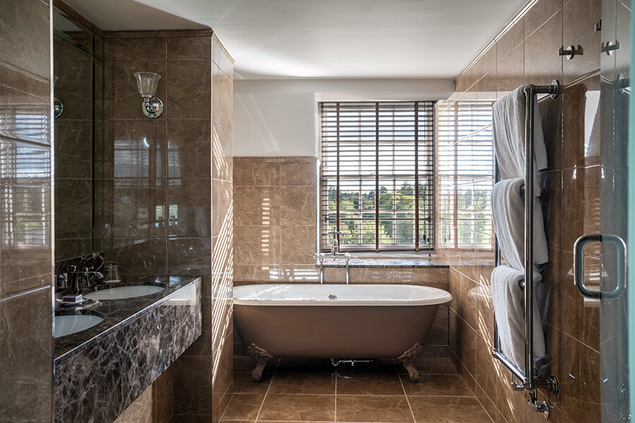 A rolltop bath sits at the end of a large bathroom with brown marble walls and floor