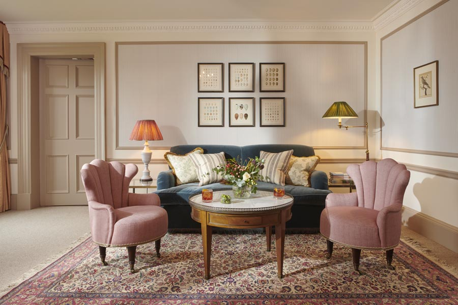 A sitting room on a whisky suite at Gleneagles with pink arm chairs and a large green sofa