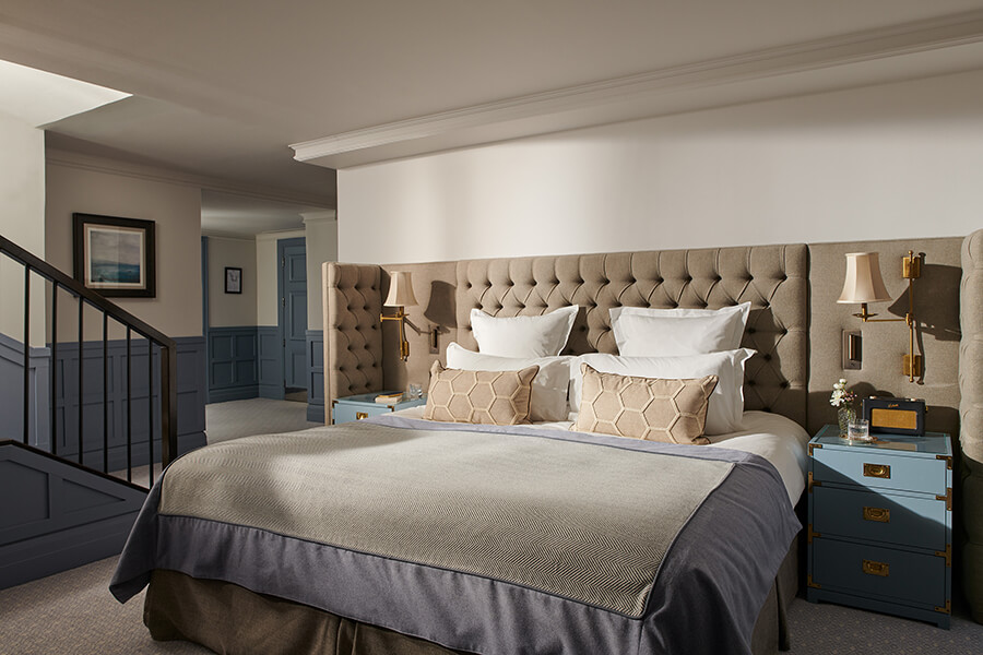 A king sized bed surrounded by a large cushioned headboard and two blue bed side chests of drawers