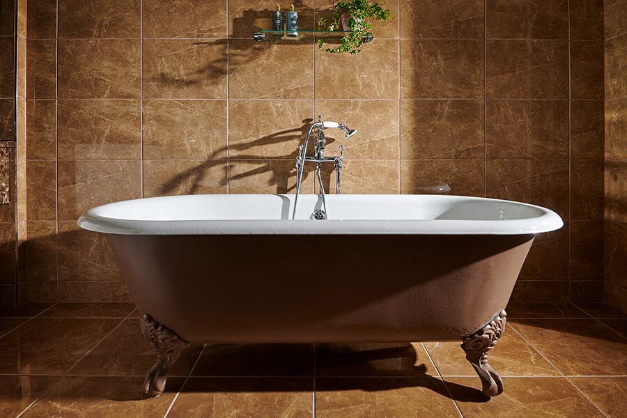 A large rollmop bath sits centrally in a brown marble bathroom