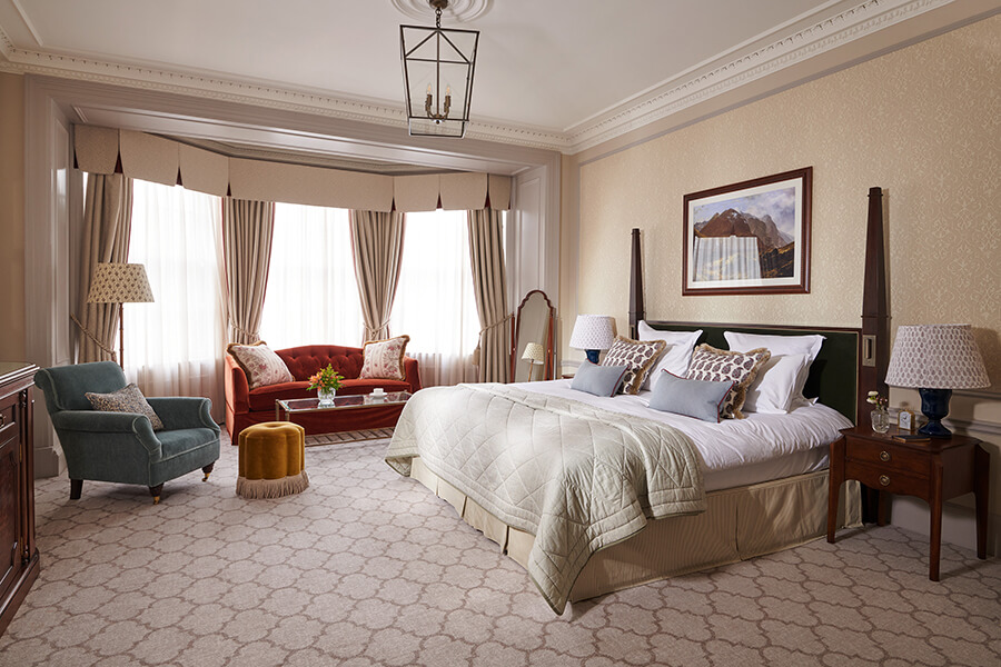 A Manor bedroom with king sized bed, red sofa and blue tub chair and large bay window