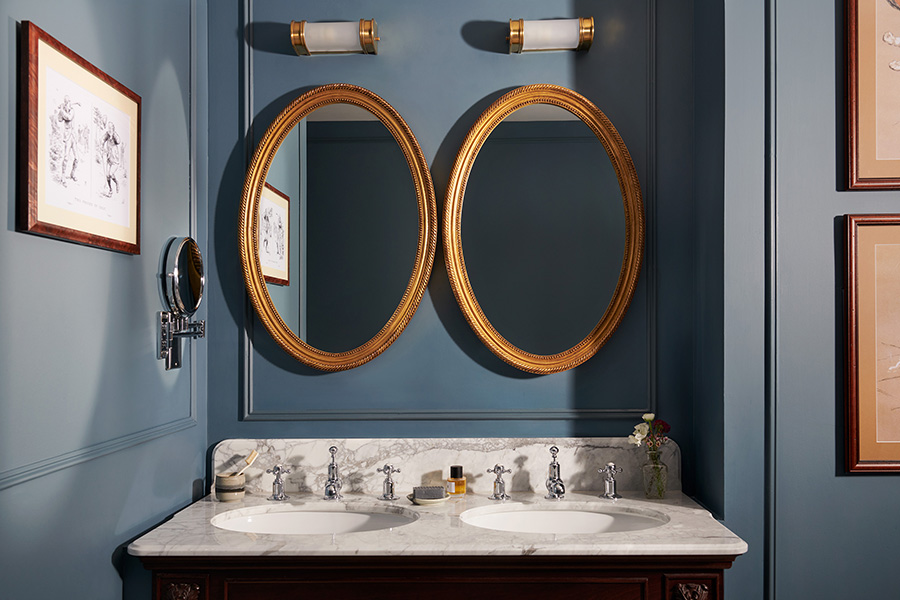 A marble double vanity bathroom sink with double oval mirror and sky blue painted walls in an estate bedroom's bathroom