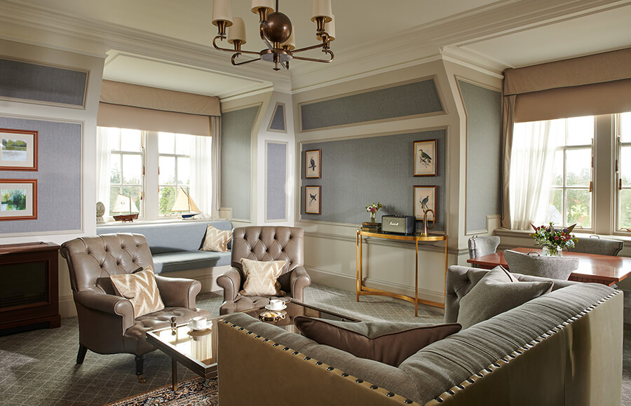 A large living room with grey leather sofa and armchairs around a glass table