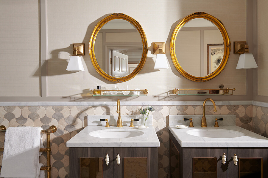 Twin marble vanity sinks with matching gold wall mirrors