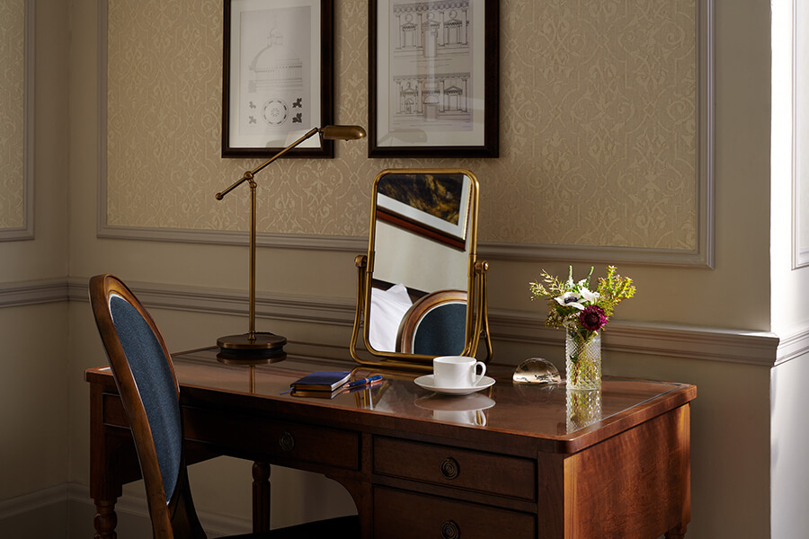 A walnut dressing table with brass mirror, reading lamp and cup and saucer of coffee in a Country bedroom