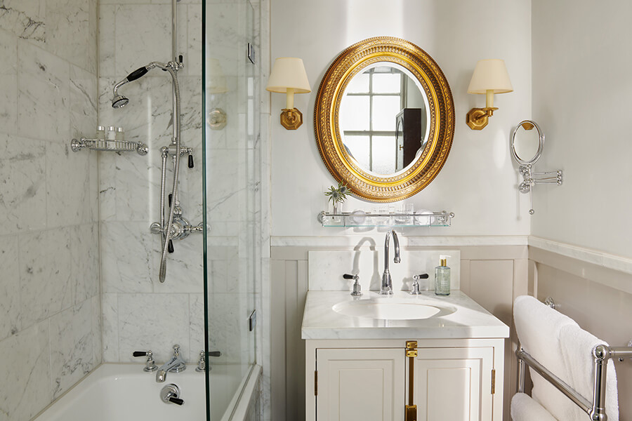 A marble shower above a large bath next to a single sink with gold mirror in a Country bedroom