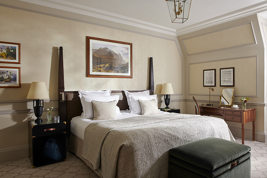 An elegant king sized bed with a painting of a mountain landscape above it sits in the middle of a luxury Country bedroom