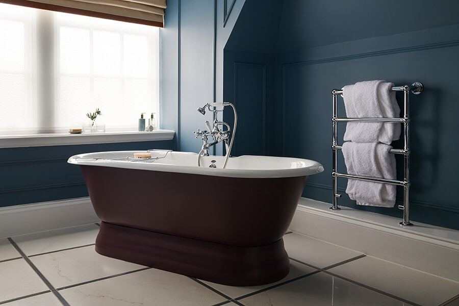 A large purple rolltop bath in the corner of a dark blue bathroom in a Manor Bedroom