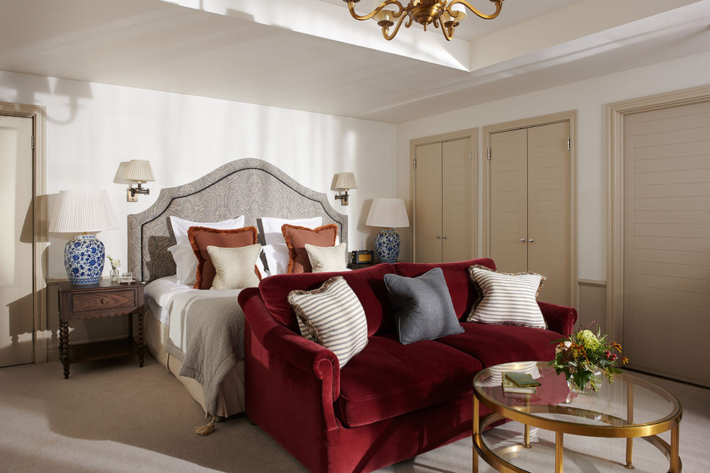 A large red sofa sits at the bottom of a king sized bed in a Braid Estate bedroom with numerous luxury lights, tables and ornaments