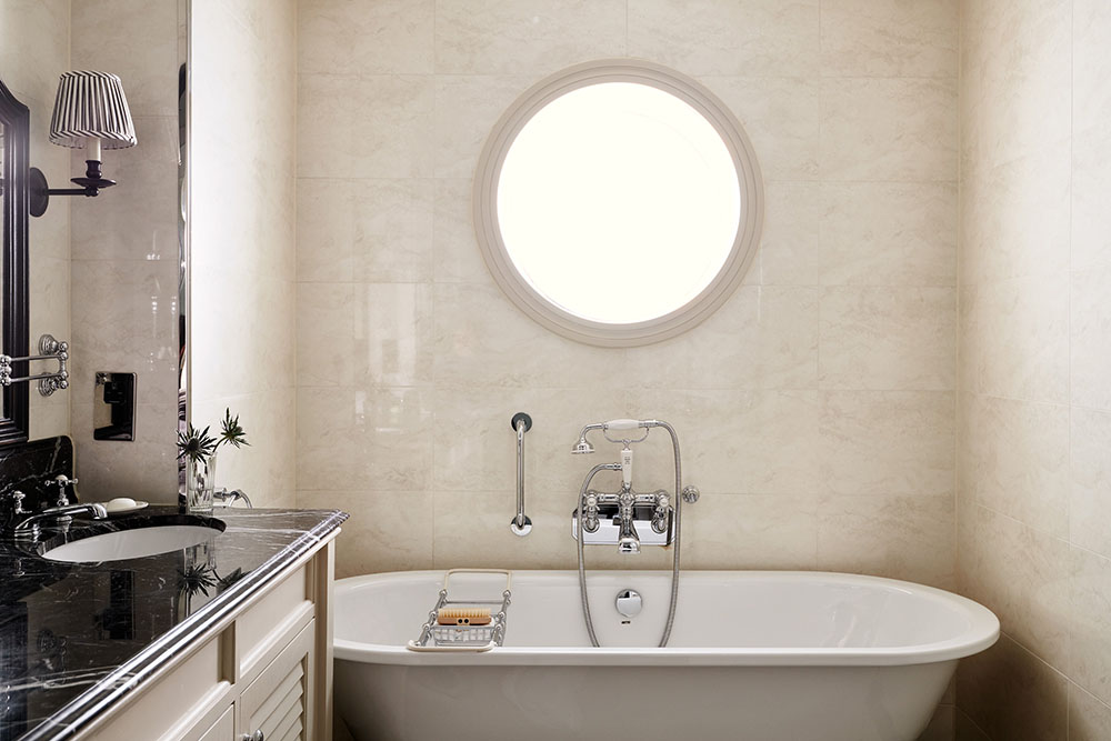 A large roll top bath with large circular window above it in a Braid Estate Bedroom's bathroom