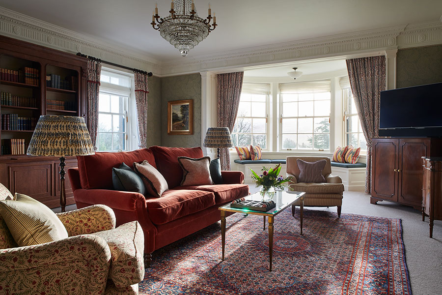 The living room in the Royal Suite with large seating area, book cases and seating in a bay window