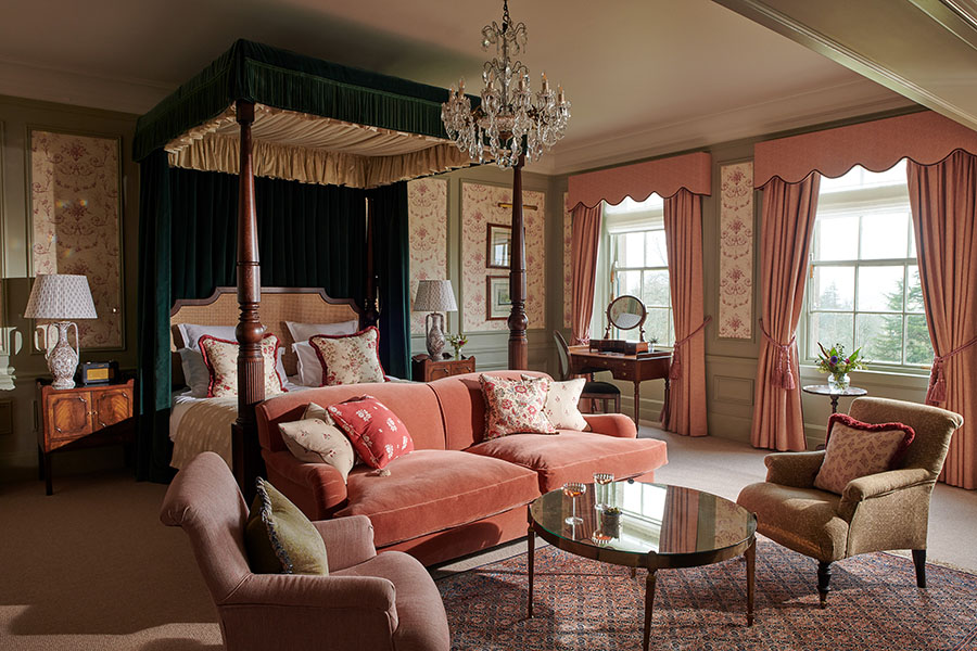 A grand four-poster bed sits in the middle of the Royal Lochnagar Suite bedroom with seating area