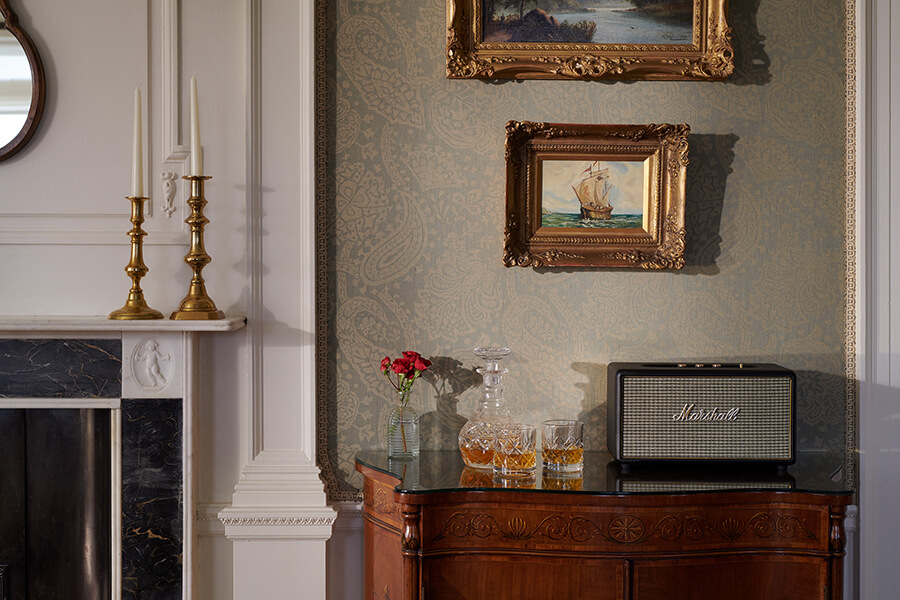 A crystal decanter and glasses with whisky in them it on top of a walnut chest of drawers with stereo speaker behind