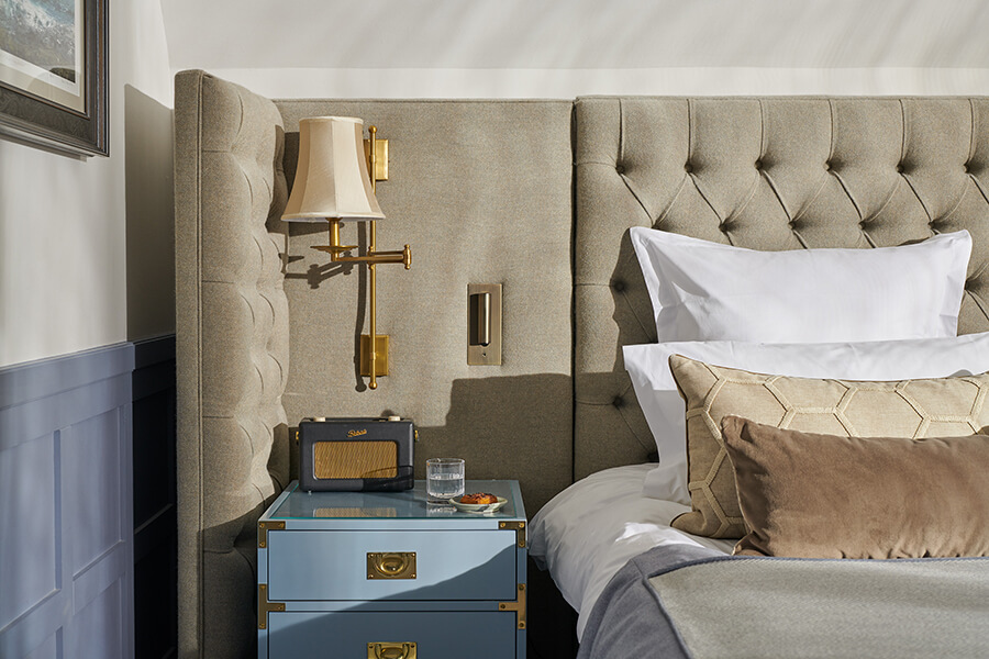 A close up of pillows on a bed and a blue bedside chest of drawers with Roberts radio on top