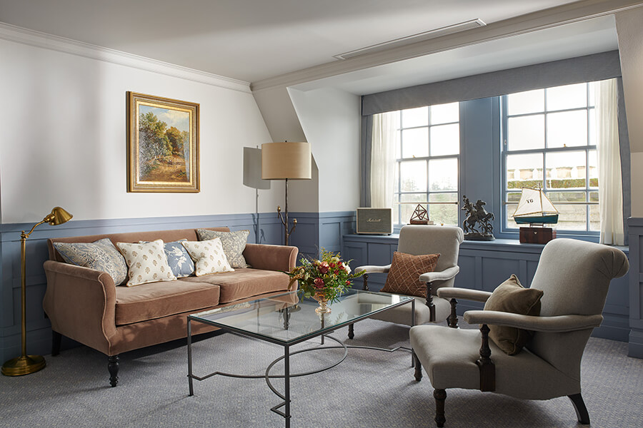 A large blue living room with glass coffee table, pink sofa and two grey armchairs