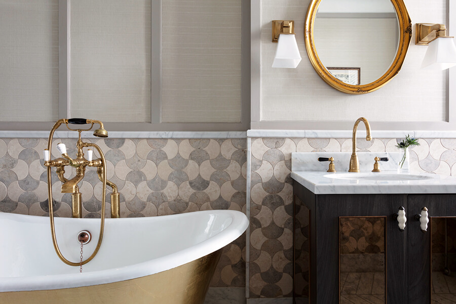 A gold rolltop bath, marble sink and gold wall mirror