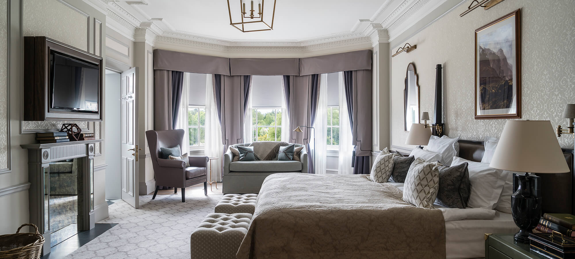 A large Estate bedroom with bay window, king sized bed and ample seating