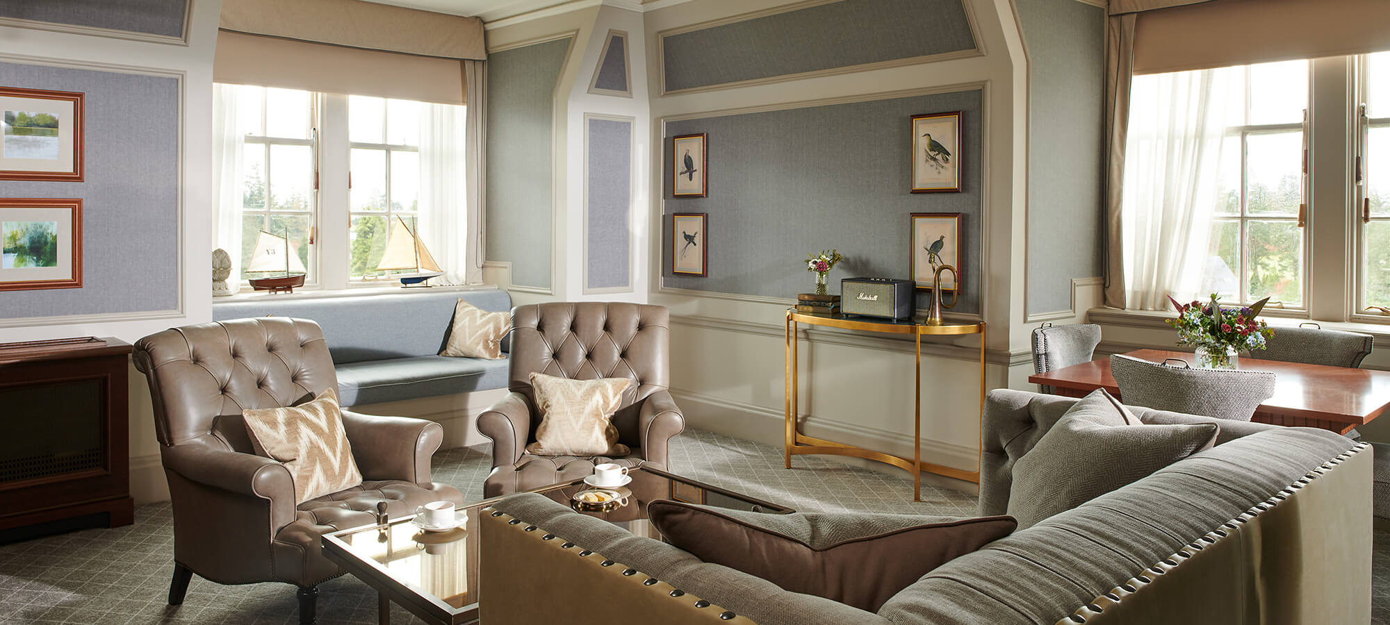 A large sitting room in a suite with two grey leather Chesterfield chairs in an estate suite