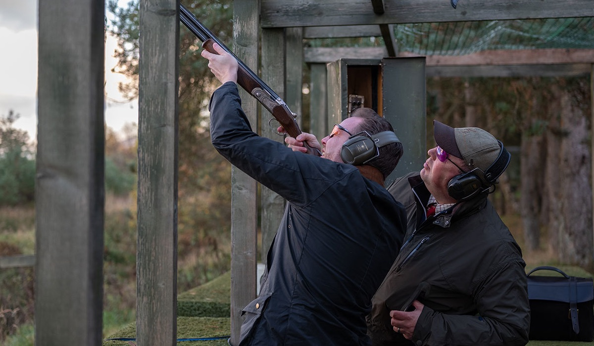 An shooting instructor helps a client aim at a target high above them