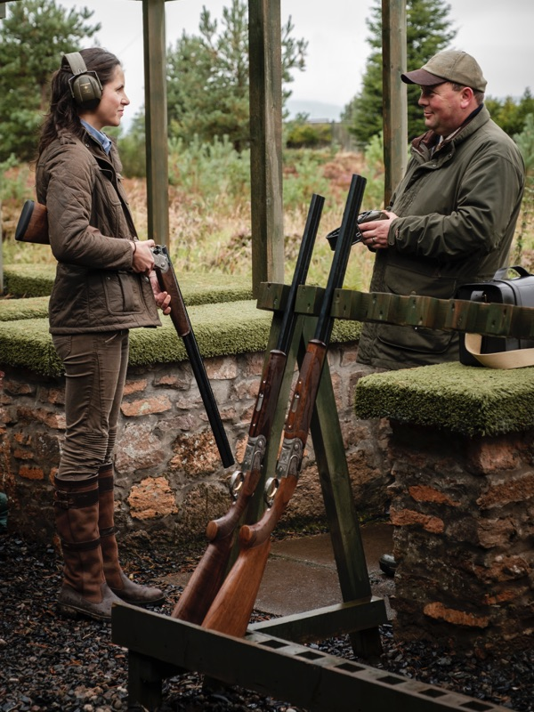 A woman speaks to a shooting instructor on a shooting range with a rack of shotguns next to them