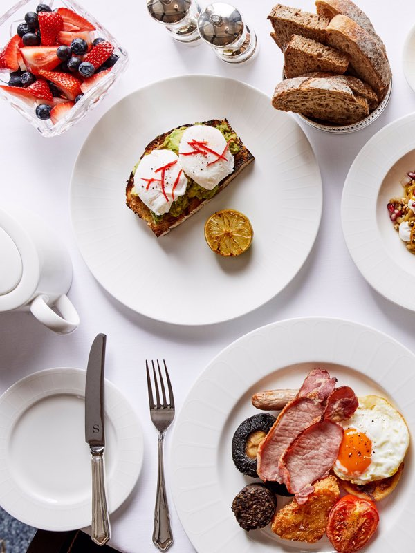 Poached egg and avocado, full Scottish breakfast, a berry fruit salad and toast on a table