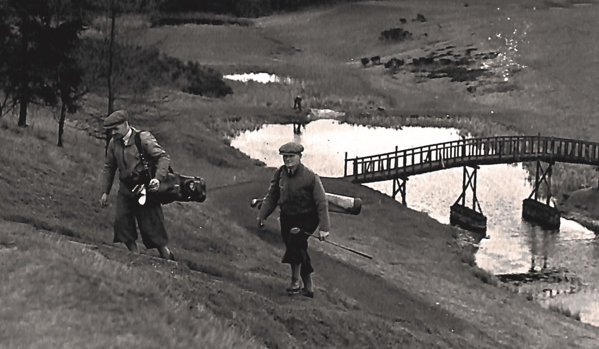 A black and white vintage photo shows two golfers playing the Queen's course at Gleneagles