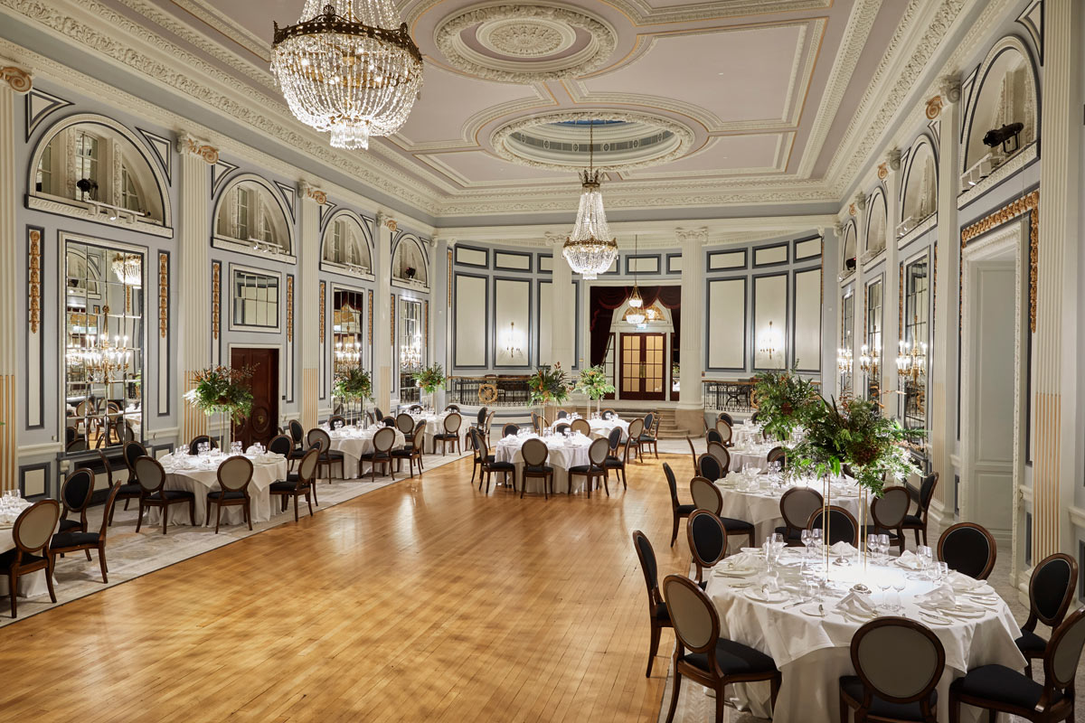 A huge ballroom with wooden floor, round tables, chandeliers and large floral arrangements at Gleneagles