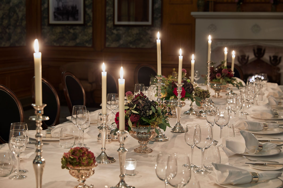 A candle lit silver service on a large table in the billiard room