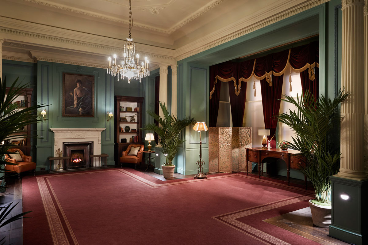 Red carpet, green walls, tow fireplaces and numerous antiquities in the Parlour room at Gleneagles