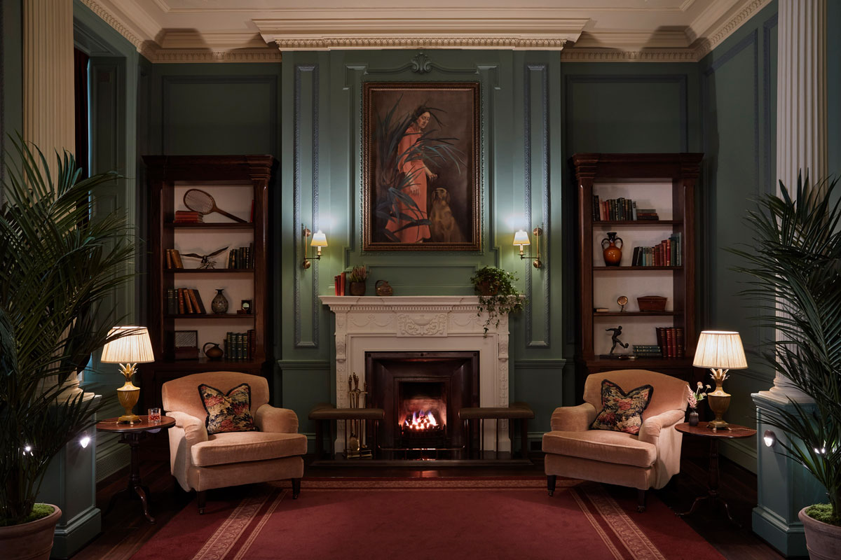 Two arm chairs sit next to an open fire in the ornate parlour room at Gleneagles