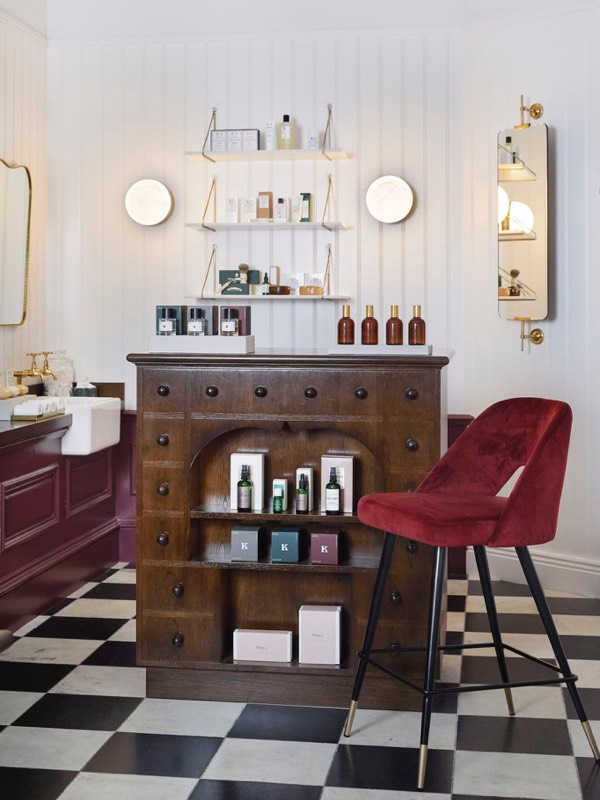 A red chair next to a cabinet with beauty products in the Gleneagles arcade