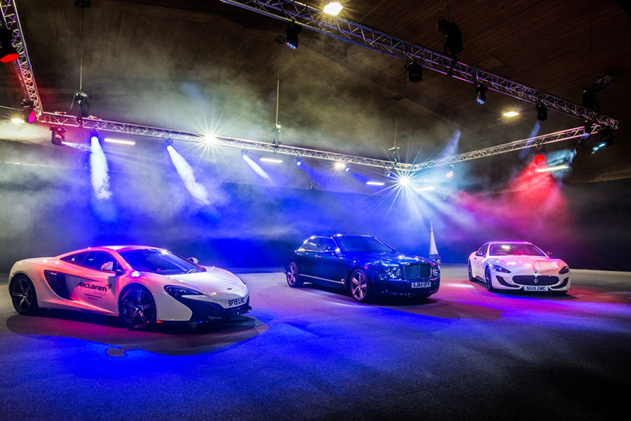 Three luxury cars sit in the middle of a large arena