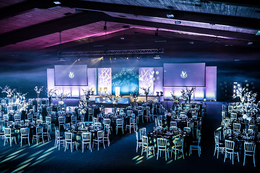 A large arena set up for dinner with presentation screens and bright lights