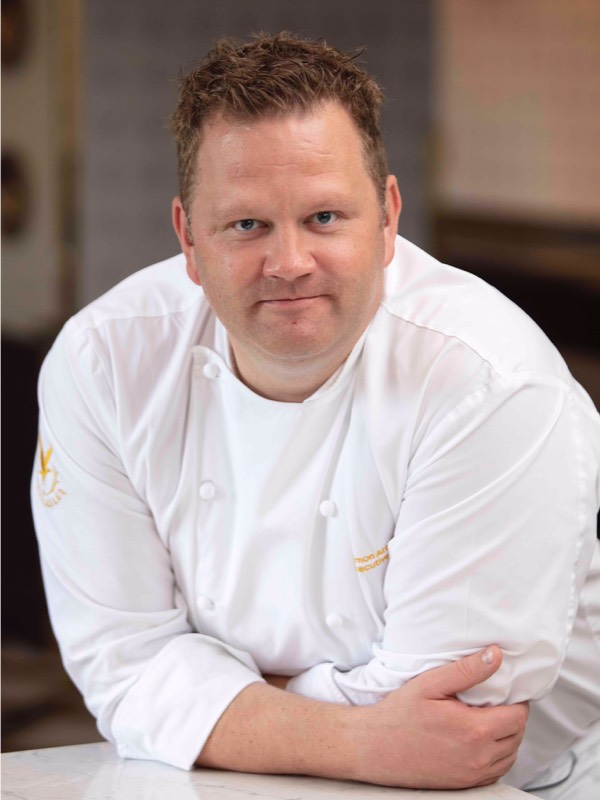 Simon Attridge in chefs whites leans on a marble table