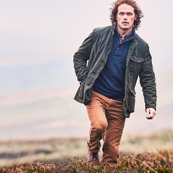 Sam Heaughan walking across a heather moorland