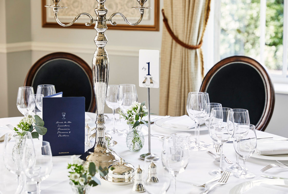A table laid for silver service with silver candelabra in the drawing room