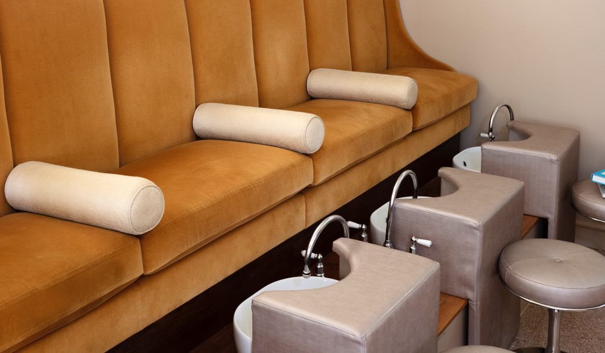 A pedicure station with yellow velvet seating and grey leather footstools