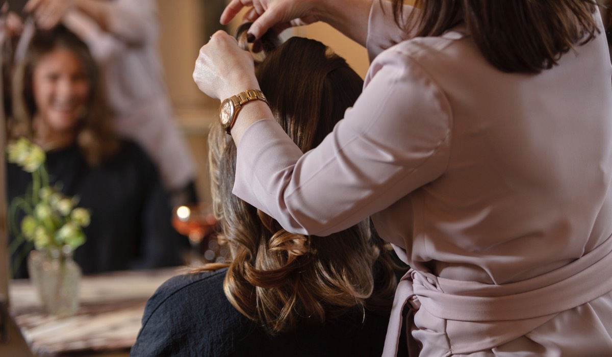 A hairdresser cuts a clients hair in Bob & Cloche