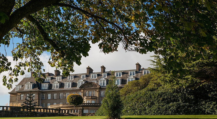 The exterior of Gleneagles shot through trees