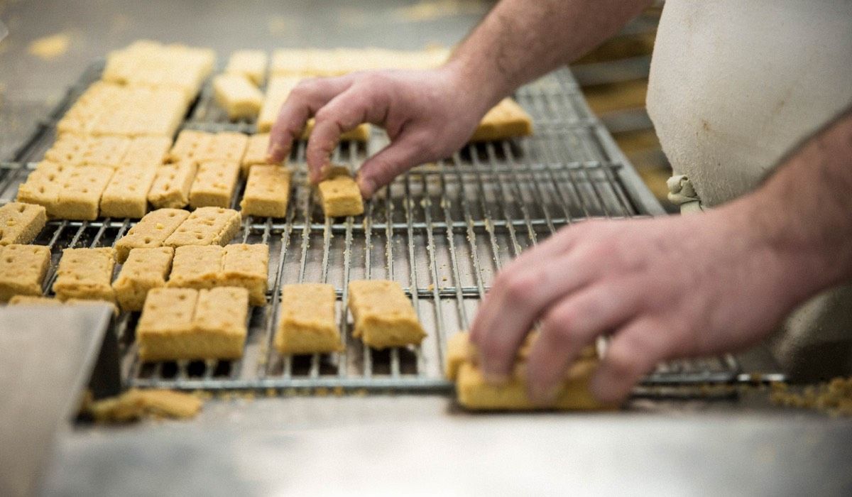 A man taking bars of shortbread off a rack in a kitchen