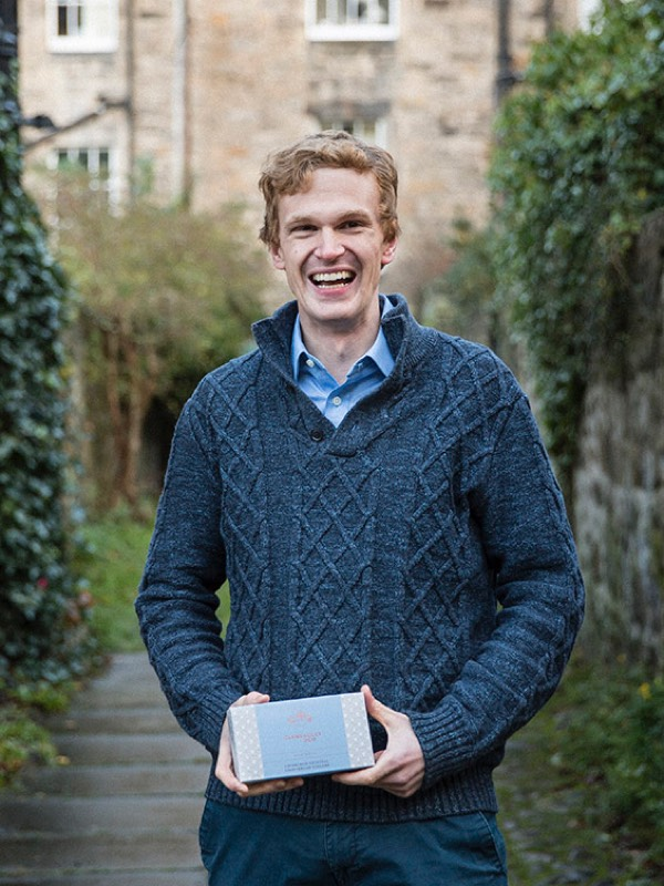 A smiling man with a blue jumper looks at the camera with a box of shortbread in his hands