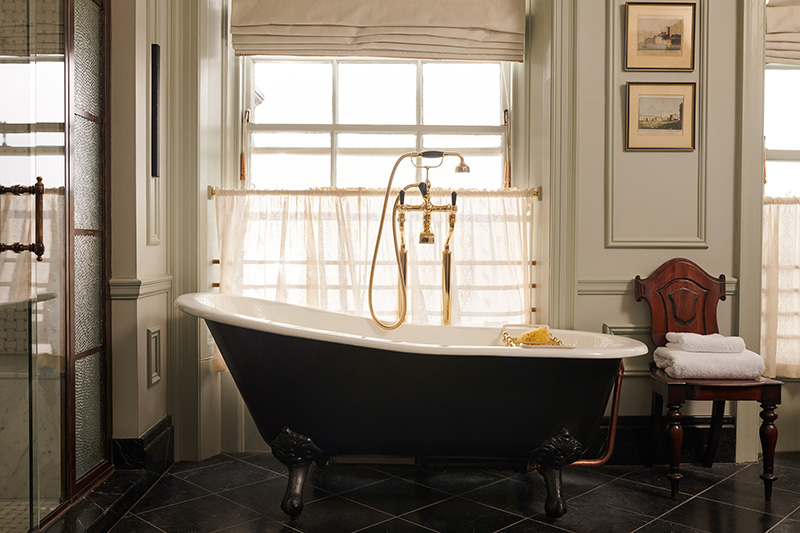 A large free-standing rollmop bath with gold taps and shower head