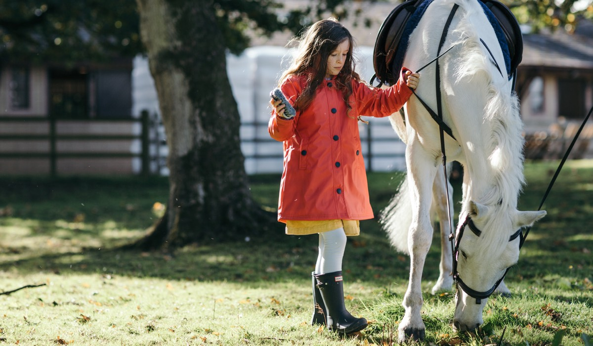 A young girl in a red jacket pats her pony