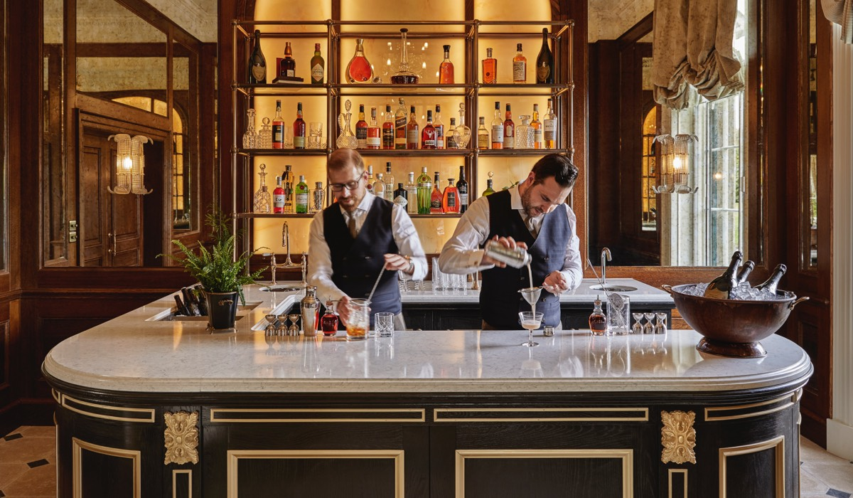 Two barmen serve drinks in the bar of the drawing room at Gleneagles
