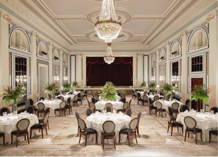 The gleneagles ballroom set up with around tables of 10 for dinner with large floral arrangements and grand chandeliers