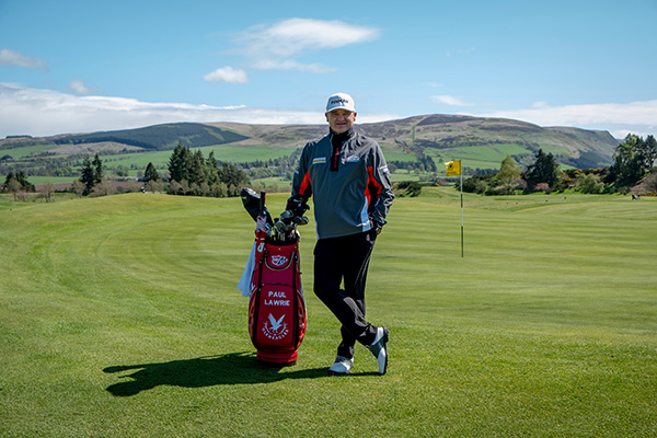 Lawrie stands on the King's course at Gleneagles on a sunny day with a Gleneagles branded god bag