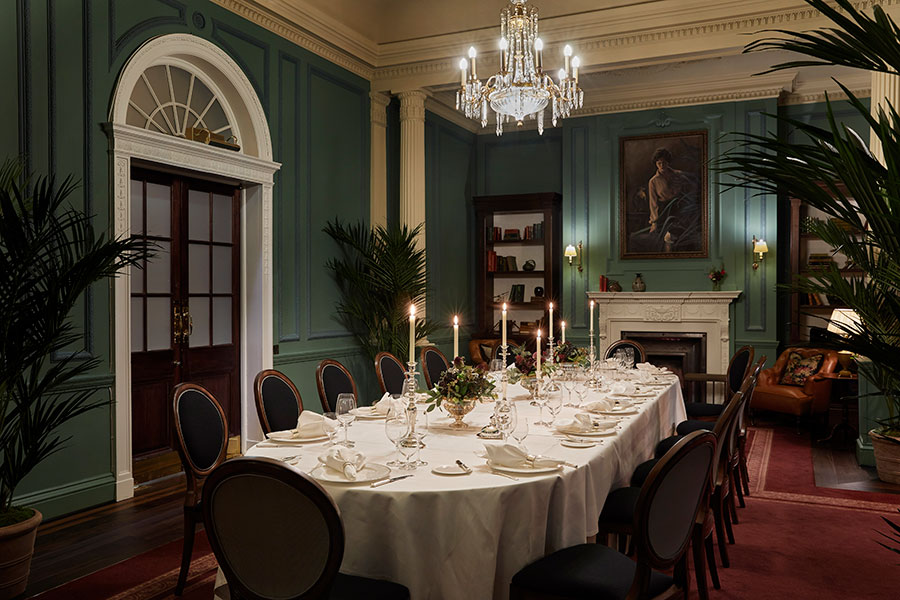 The parlour room set up for a silver service candlelit dinner for fourteen