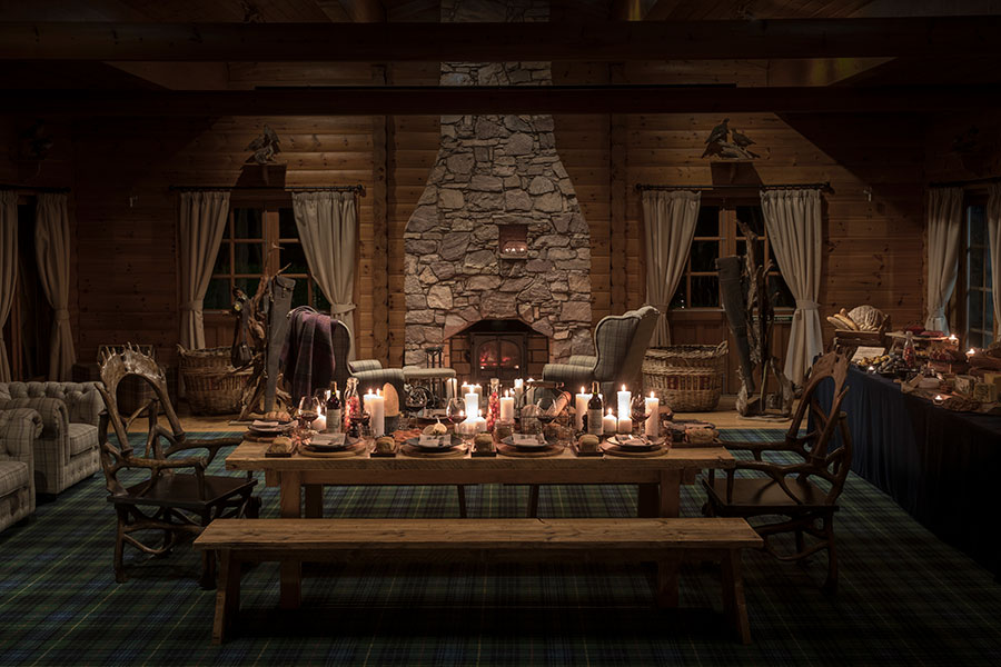 An atmospherically lit shooting lodge set for a private dinner at night